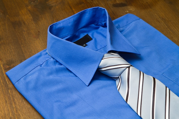 La camicia e il legame del nuovo uomo blu isolati su legno
