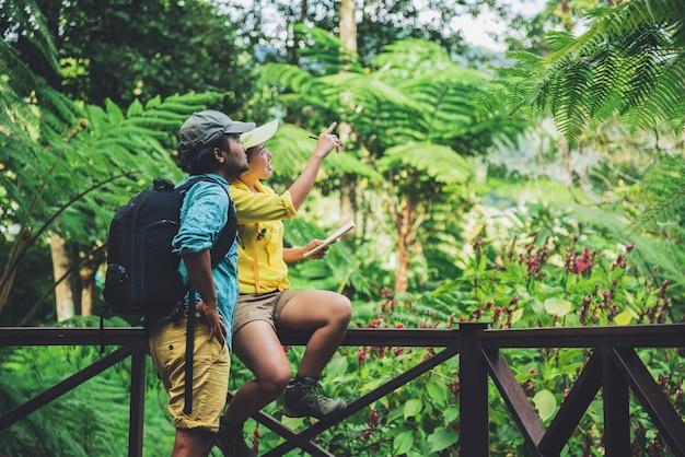 La camminata asiatica della natura di viaggio delle coppie si rilassa e studia la natura nelle parti anteriori.