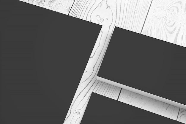 La cancelleria di carta nera in bianco ha messo sulla vista di clode-up dello scrittorio di legno