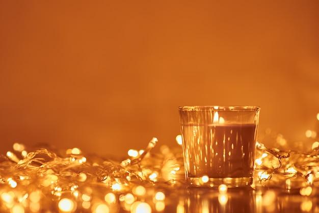 La candela bruciante con la ghirlanda dorata si accende nel bokeh su buio
