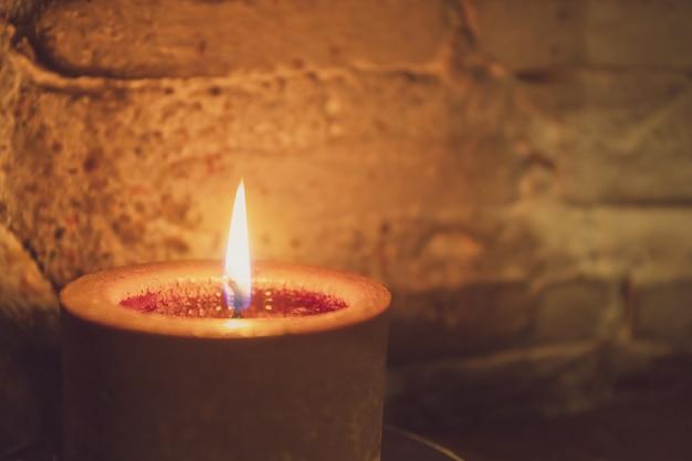 La candela era illuminata sull'altare con lo sfondo del muro di mattoni.