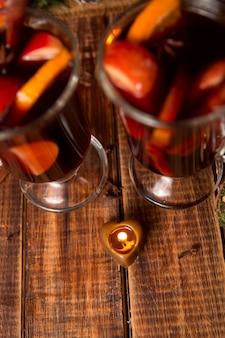 La candela gradisce il cuore vicino al vin brulé su fondo di legno. natale.