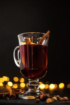La cannella si trova in un bicchiere, primo piano bicchiere di vin brulè con arancia e cannella su sfondo nero scuro