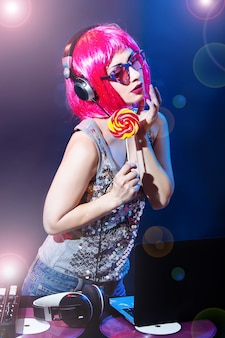 La caramella del disco del vinile della cuffia del ritratto dj gioca l'attrezzatura l'estate della ragazza della discoteca del partito i retro dolci di giovane donna di fascino del miscelatore di scrittorio rosso rosa dell'annata