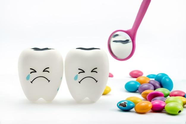 La carie dentaria sta piangendo con lo specchio dentale e il cioccolato ricoperto di zucchero sul lato. su bianco
