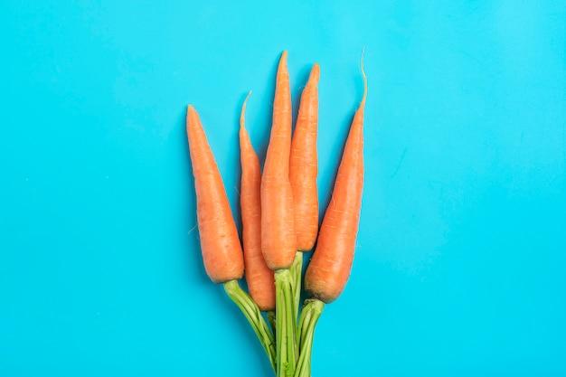 La carota organica naturale raccolta fresca si trova su fondo blu