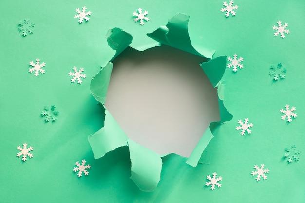 La carta blu piatto giaceva con fiocchi di neve e buco strappato con copia-spazio su bianco pape, sfondo di natale