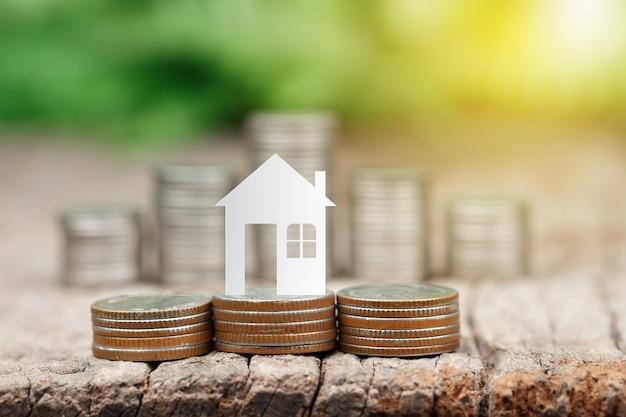 La carta della casa sulle monete impila per il risparmio per comprare una casa