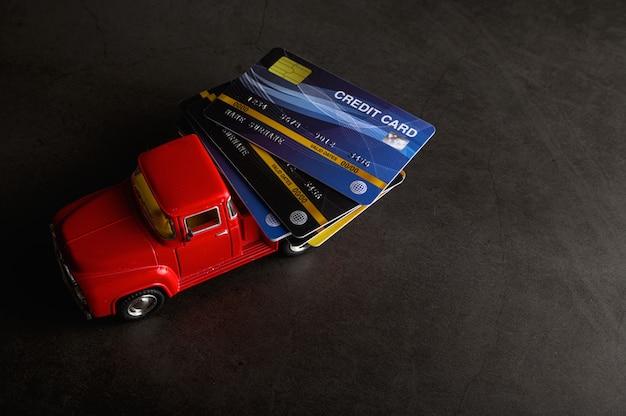 La carta di credito sul modello di pickup rosso sul pavimento nero