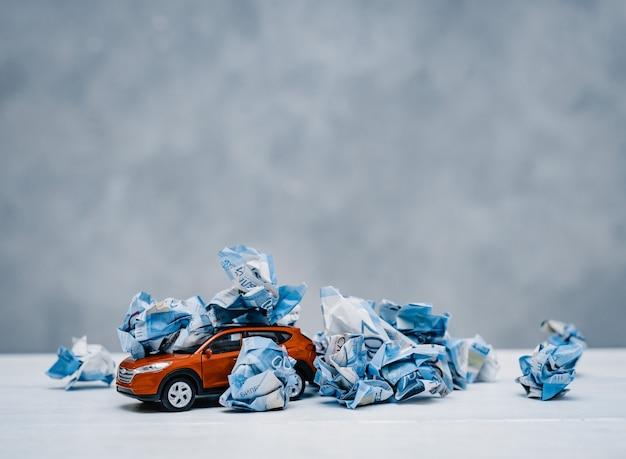 La carta ha sgualcito i soldi in un barattolo di vetro su un concetto blu del fondo per risparmiare e risparmiare soldi per un'automobile