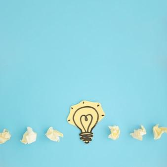 La carta ha tagliato la lampadina gialla con carta sgualcita su fondo blu