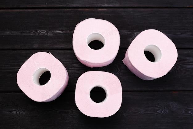 La carta igienica di rosa pastello rotola sulla tavola di legno nera