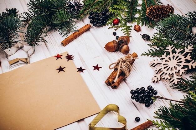 La carta rustica si trova al centro di un cerchio fatto di rami di abete e decorazioni natalizie rustiche