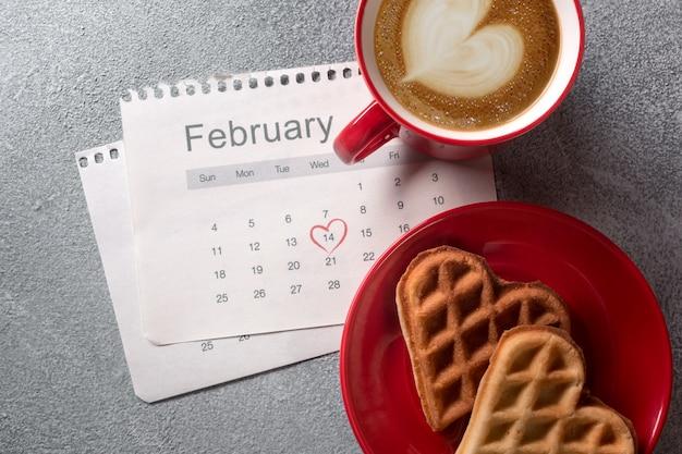 La cartolina d'auguri di san valentino con la tazza di caffè ed il cuore hanno modellato i biscotti su fondo grigio.