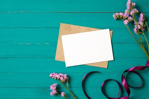 La cartolina d'auguri e la busta in bianco con la margherita porpora fiorisce sulla tavola di legno verde. composizione piatta, vista dall'alto, dall'alto.