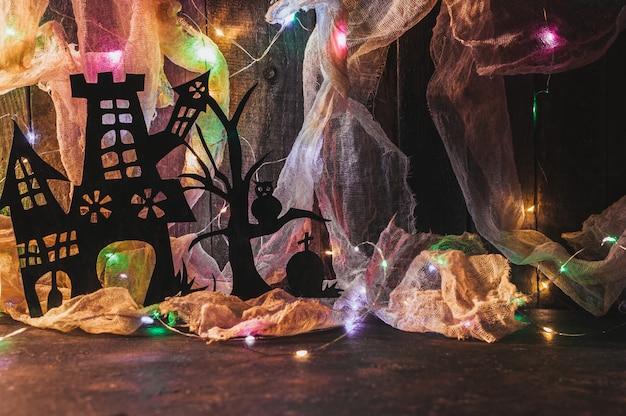 La casa della strega con una tomba e un albero spaventoso ritagliati di carta nera su una parete di legno con una ragnatela.