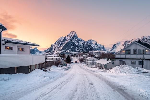 La casa ha coperto la neve con la strada circondata con la montagna al tramonto