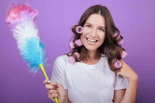 La casalinga allegra in bigodini rosa rispolvera con un pipidaster.