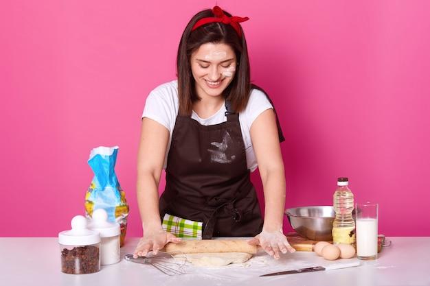 La casalinga o il panettiere felice indossa il grembiule della cucina sporco con farina, maglietta bianca