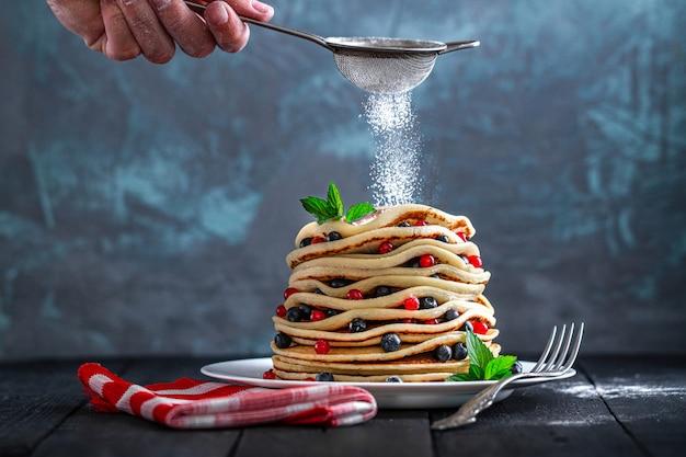 La casalinga spruzza lo zucchero a velo sui pancake fatti in casa al forno con le bacche e la menta fresche per la prima colazione dolce deliziosa