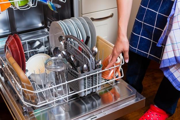 La casalinga sta lavando i piatti con la lavastoviglie