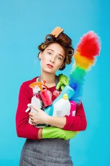 La casalinga stanca in attrezzatura rosa tiene lo spolveratore e gli strumenti di pulizia