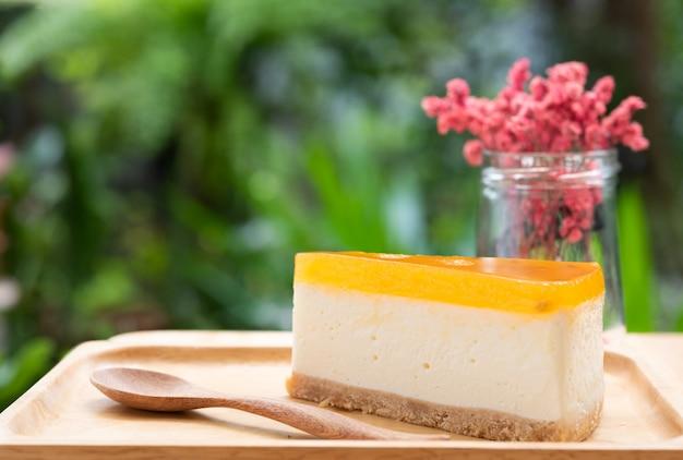 La cheesecake del frutto della passione serve su legno tay e sulla tavola di legno con il fiore secco
