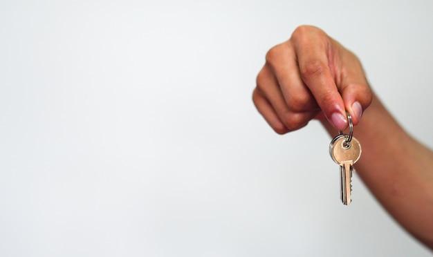 La chiave della casa della tenuta della mano dell'uomo su fondo bianco