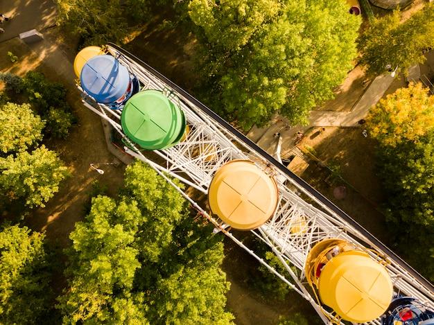 La cima aerea direttamente sopra la vista della ruota panoramica nel parco pubblico della città di divertimento dell'estate, drone ha sparato d