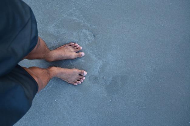 La cima dei piedi dell'uomo senza scarpe sulla sabbia