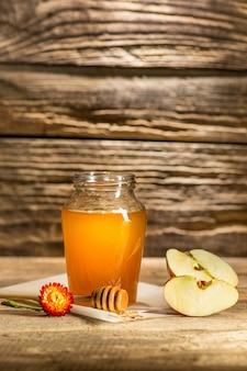 La ciotola con miele sulla tavola di legno. la banca del miele resta vicino al cucchiaio di legno