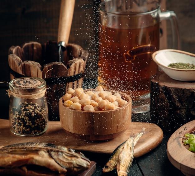 La ciotola di ceci viene versata con sale per la preparazione della birra