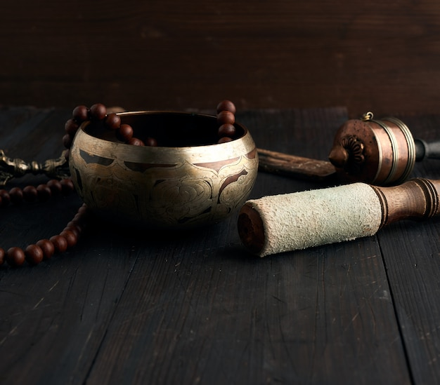 La ciotola tibetana di rame di canto con una valvola di legno su un marrone corteggia