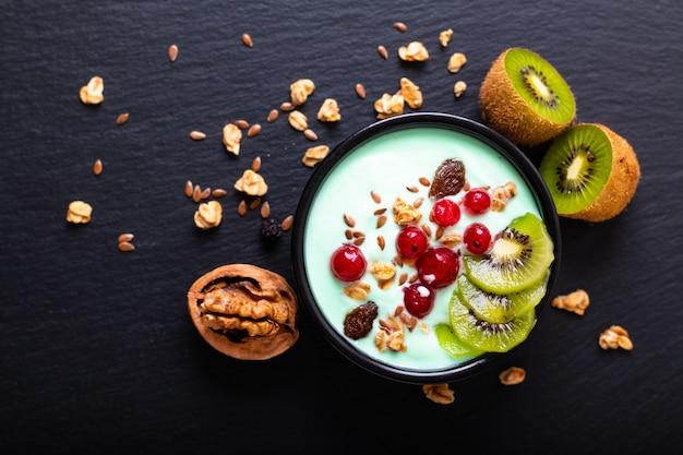 La ciotola variopinta della prima colazione del yogurt dell'alimento sano fruttifica guarnizione con lo spazio della copia