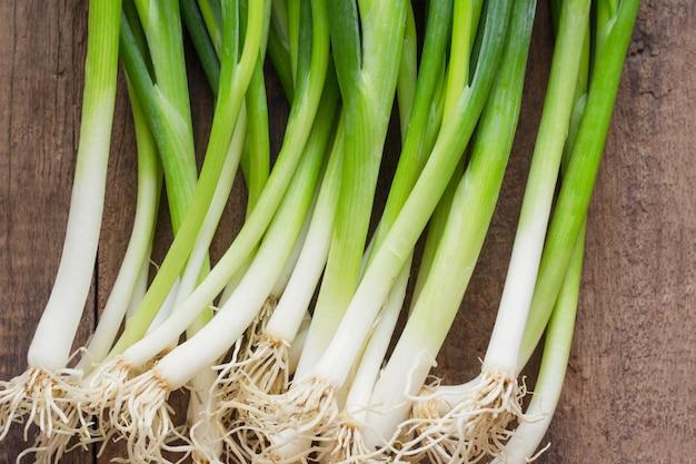 La cipollina fresca o scalogno sulla plancia di legno nella disposizione del piano di vista superiore prepara per cucinare.