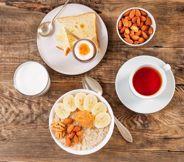 La colazione al mattino, su un tavolo di legno, vista dall'alto. un bicchiere di latte, tè, farina d'avena con