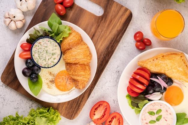 La colazione comprende croissant, uova fritte, condimento per insalata, uva nera e pomodori.