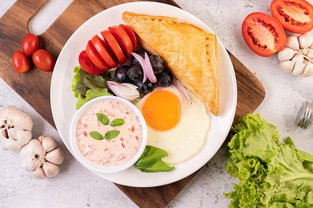 La colazione comprende pane, uova fritte, condimento per insalata, uva nera, pomodori e cipolle affettate.