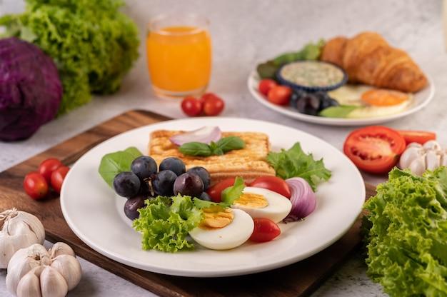 La colazione comprende pane, uova sode, condimento per insalata di uva nera, pomodori e cipolle affettate.