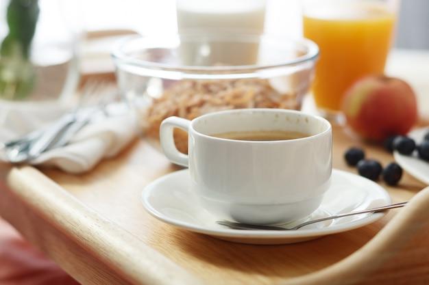 La colazione è servita a letto sul vassoio in legno con caffè e cornetti