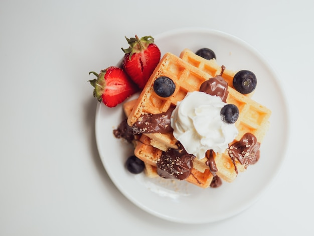 La colazione era piatta. waffle gustoso con frutta, cioccolato e panna montata su un piatto di ceramica bianca