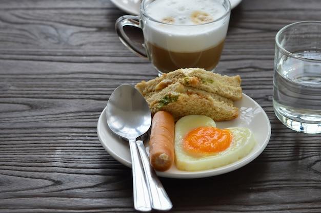 La colazione sul tavolo include uova fritte, salsicce, panini e caffè.