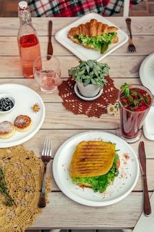 La colazione viene servita al tavolo del caffè con frittelle di formaggio, sandwich, cornetti e bevande. vista dall'alto