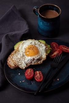 La colazione viene servita con caffè, pane, uova fritte, avocado e pomodori