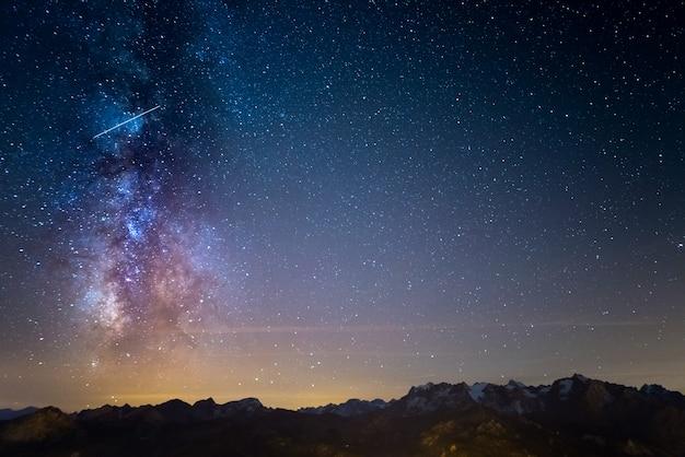 La colorata via lattea luminosa e il cielo stellato sulle alpi francesi e il maestoso massiccio degli ecrins.