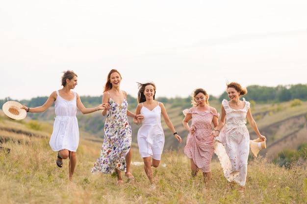 La compagnia di allegre amiche si diverte insieme a fare un picnic in un luogo pittoresco che si affaccia sulle verdi colline. ragazze in abiti bianchi che ballano nel campo