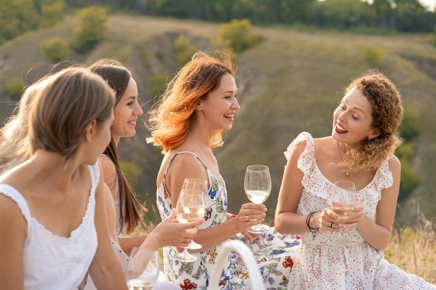 La compagnia di bellissime amiche che si divertono, bevono vino e si godono un picnic nel paesaggio collinare