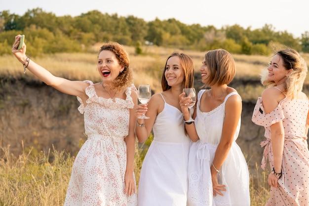 La compagnia di eleganti amiche felici che si divertono e fanno selfie con bicchieri di vino all'esterno