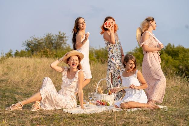 La compagnia di eleganti amiche felici che si divertono sulla festa all'aperto in stile retrò