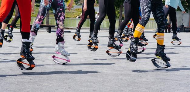 La compagnia di ragazze giovani e attraenti è impegnata nell'aerobica all'aria aperta. uno stile di vita sano. primo piano di scarpe sportive.